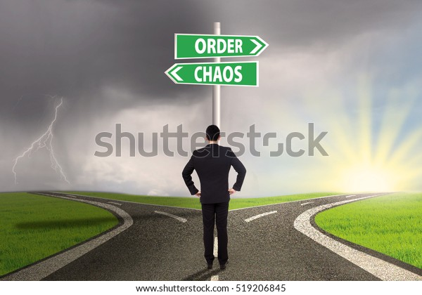 Businessman standing on the road looking at signpost of order and chaos