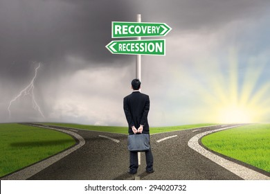 Businessman standing on the road while looking at the road sign guide to recession and recovery finance