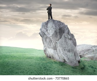 Businessman standing on a rock and observing the panorama