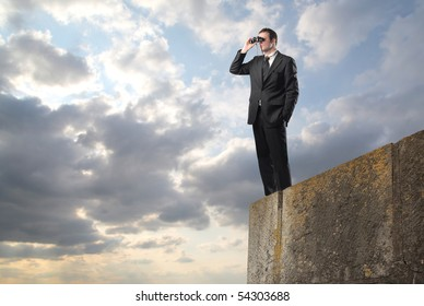 Businessman standing on a rock and using binoculars