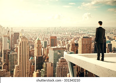 Businessman standing on the roof of a skyscraper and looking over the city at sunset