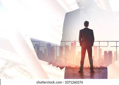 Businessman standing on rooftop and looking into the distance. Research and communication concept. Double exposure