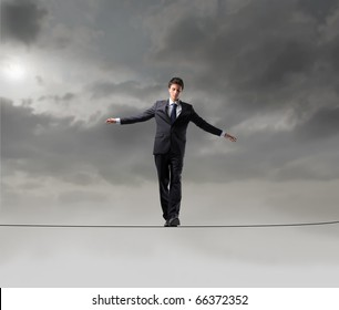 Businessman standing on a rope over the void
