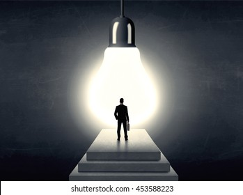 Businessman standing on a step in front of a huge light bulb, concept of having an idea.