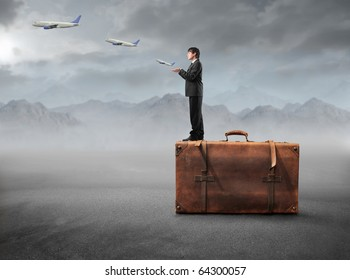 Businessman standing on a suitcase with airplanes flying from his hands