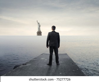 Businessman standing on a wharf with Statue of Liberty in the background