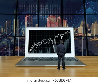 Businessman standing on the wood table which have the computer laptop showing the trading graph at the screen over the blurred photo of trading graph on cityscape background, Business trading concept