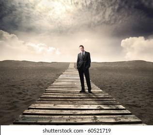 Businessman standing on a wooden path on a desert