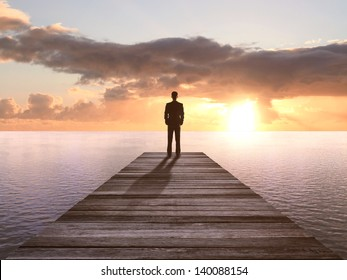 businessman standing on wooden pier at a sunset