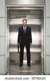 Businessman standing in open Elevator, portrait, front view