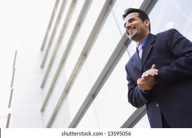 Businessman standing outside modern office building
