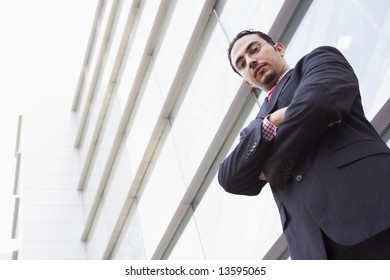 Businessman standing outside office block looking to camera