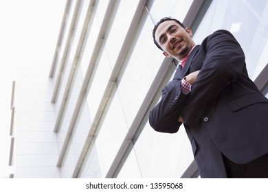 Businessman standing outside office building looking to camera