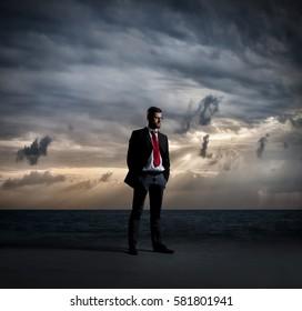Businessman standing over dark, dramatic ocean background. Business concept.