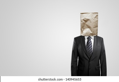 businessman standing with paper bag on head isolated on white