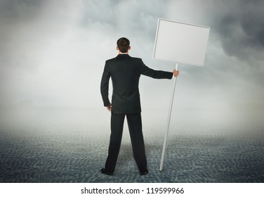 Businessman standing with a placard in his hand