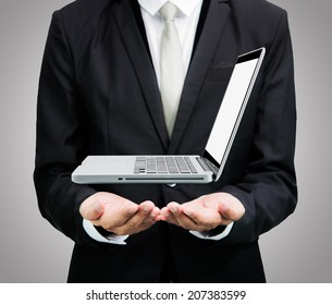 Businessman standing posture hand hold laptop isolated on over gray background