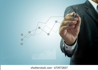 Businessman standing posture hand hold pen drawing graphics a growing graph over blue background