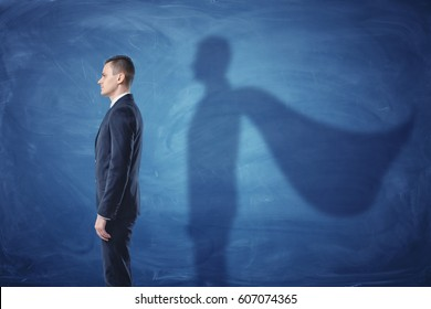 Businessman is standing in profile casting a shadow of the superman's cape on blue chalkboard background. Inner strength. Leader's qualities. Ready for profit and development