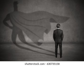 Businessman is standing in profile casting a shadow of the superman's cape on grey chalkboard background. Inner strength. Leader's qualities. Ready for profit and development