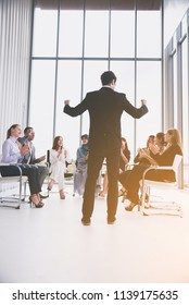 businessman standing raising his hand during presentation and attendees sit in a row half circle are talking in business meeting