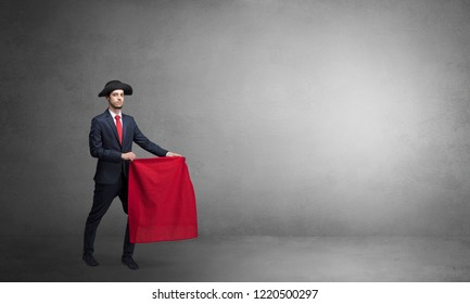 Businessman standing with red toreador cloth in his hand in an empty room