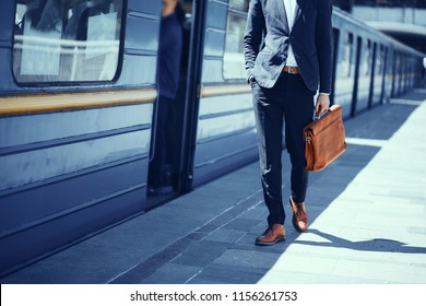Businessman standing at subway platform. Elegant guy in formal suit and brown leather shoes standing at metro station waiting for train to arrive.