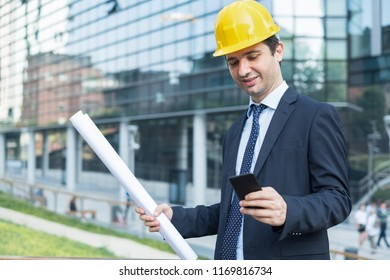 Businessman standing in suit on the construction site using smartphone app
