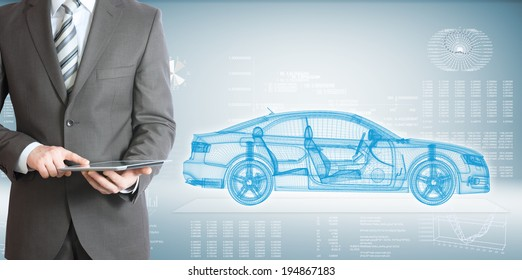 Businessman standing with tablet pc . On background of the high-tech wire frame car and graphs
