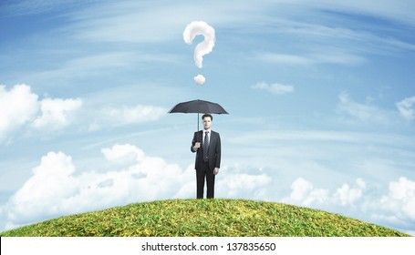 businessman standing with umbrella on field