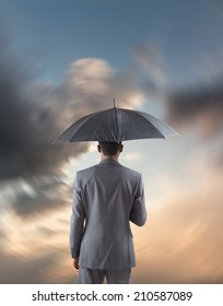 Businessman standing under umbrella against blue and orange sky with clouds