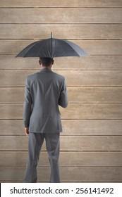 Businessman standing under umbrella against wooden planks