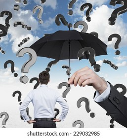 Businessman standing under the umbrella while question marks are falling down.