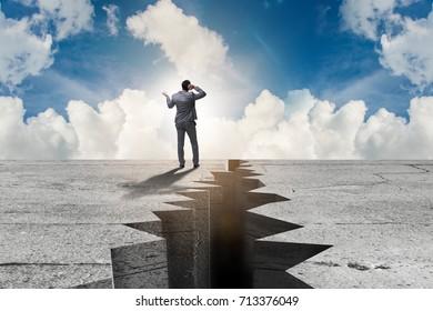 Businessman standing unsure next to cliff