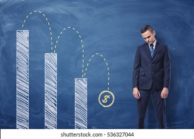 Businessman standing upset and a column diagram with a dollar sign falling down painted on the blackboard behind him. Currency falling. Crisis effect. Money loss.