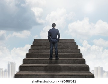 Businessman standing for walking up stairs over the cityscape under the cloud and sky background,Success business and Ambitions concept
