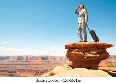 Businessman standing with a wheelie carry-on case looking out over massive red rock canyon landscape