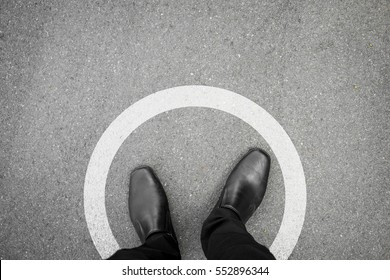 Businessman standing in white circle line feeling it is a limit and safety and never think different.