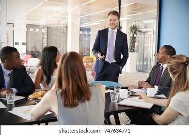 Businessman stands to address colleagues in a meeting room