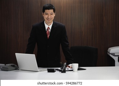 A businessman stands behind his desk