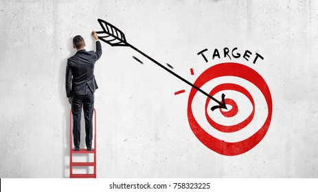A businessman stands and draws on the wall a big arrow in the center of a red archery target. Business and success. Build your future. Reach your goals.