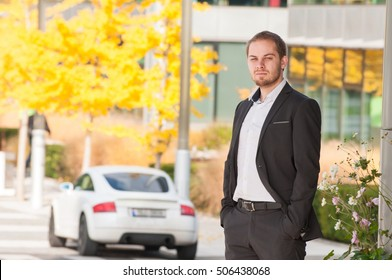 Businessman stands in front of his car. Man in suit standing near his white sport car.