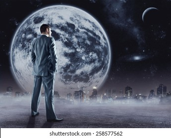 Businessman stands looking at the moon