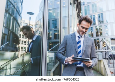 businessman stands in an office park with a tablet in the hand