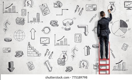 A businessman stands on a red ladder and draws financial illustrations on a while wall. Business and planning. Investment and future. Commercial development.