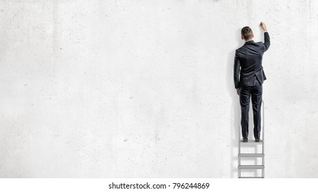A businessman stands on a step ladder in a back view and draws on an empty white wall. Business planning. Growth and strategy. Effective management.