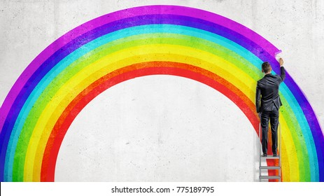 A businessman stands on a stepladder and drawing the last colorful line in the wall picture of a rainbow. Business and dreams. Uncommon and unusual plans. Different and unique vision.