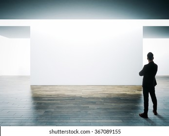 Businessman stands opposite big white wall in museum interior with wooden floor. Horizontal