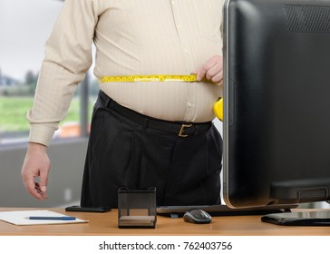 Businessman stands with tape meter in front of big monitor in the office. This man wearing black pants and beige shirt with long sleeve measures his big waist during online dietitian appointment