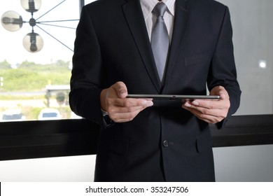 Businessman standup and use Tablet device as business concept.